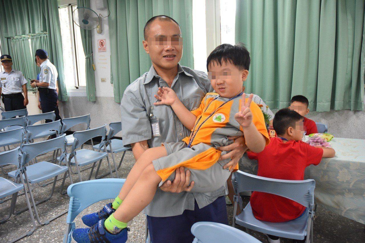 了空法師的幫助下,讓收容人子女因有獎學金鼓勵,課業更精進,收容人高興地抱起孩子,...