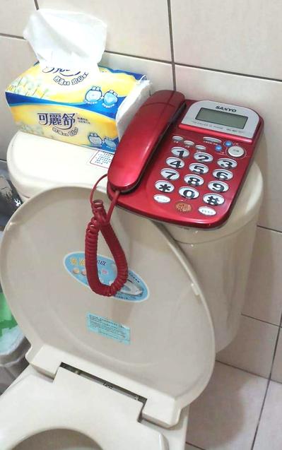 民眾在臉書PO出一張照片,由於怕上廁所錯過民調電話,將電話線牽到馬桶上方。圖/截...