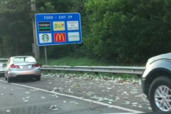 美國亞特蘭大公路發生運鈔車散落鈔票事件,許多路過車輛停在路肩撿錢。紐約時報