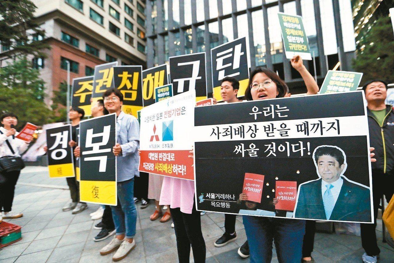 南韓大學生十一日在首爾日本大使館前抗議日本限制高科技材料出口南韓,標語寫著「我們...