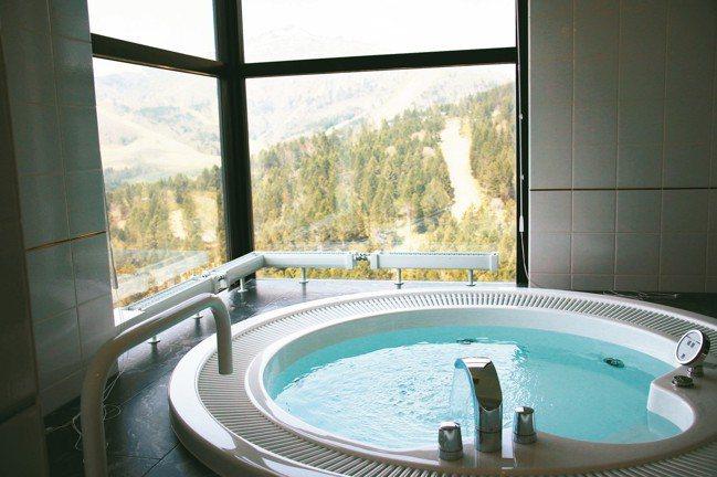 泡在按摩池裡,窗外是冬天滑雪道豪景,此時則是一片翠綠。 圖/陳志光、游慧君