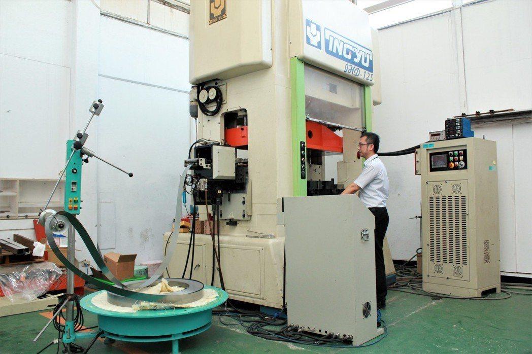 工程師操作料帶式精微成型系統進行連續沖模生產。 金屬中心/提供