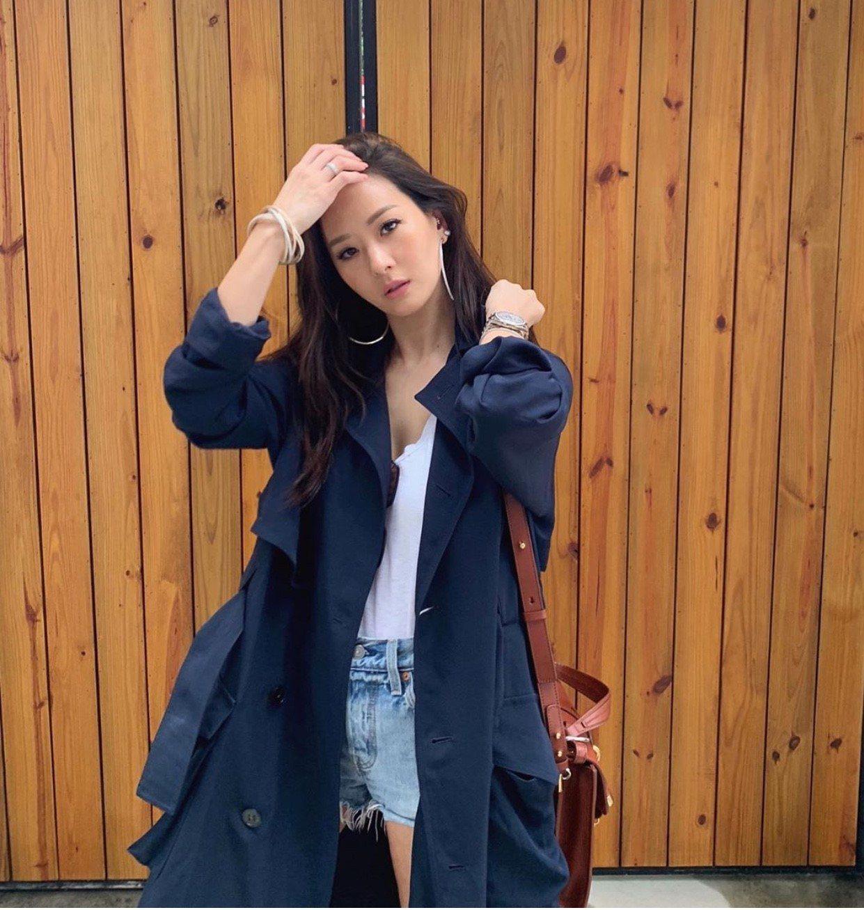 孫芸芸以長版風衣、熱辣短褲,撩髮詮釋Aby咖啡色鎖頭包。圖/取自IG