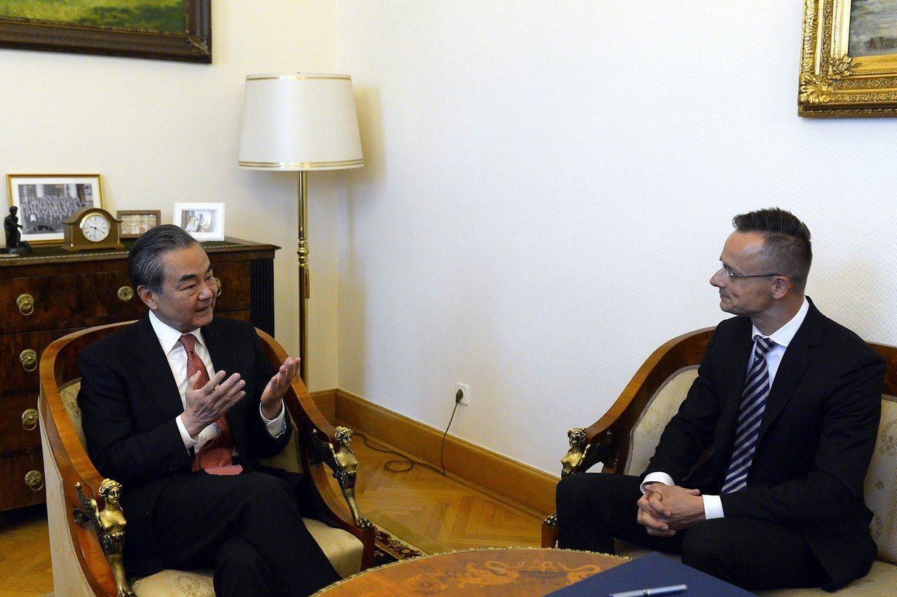 王毅(左)12日與匈牙利外貿部長Peter Szijjarto會談。歐新社