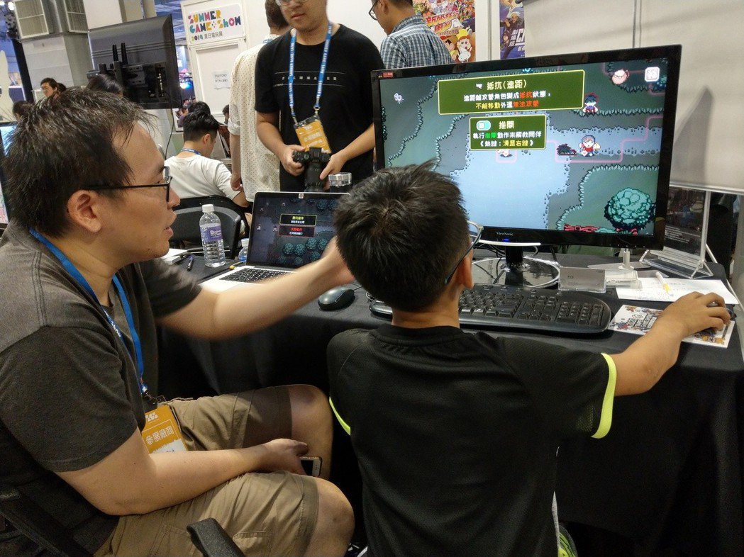 製作人陳亦威親切向小男孩介紹這款遊戲。