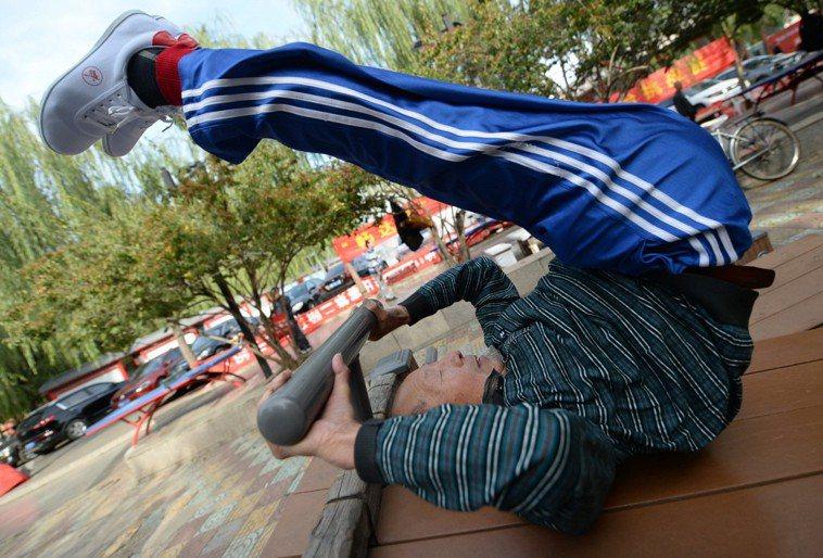 80歲健身達人在公園做雙手固定斜板收腹舉腿。新華社
