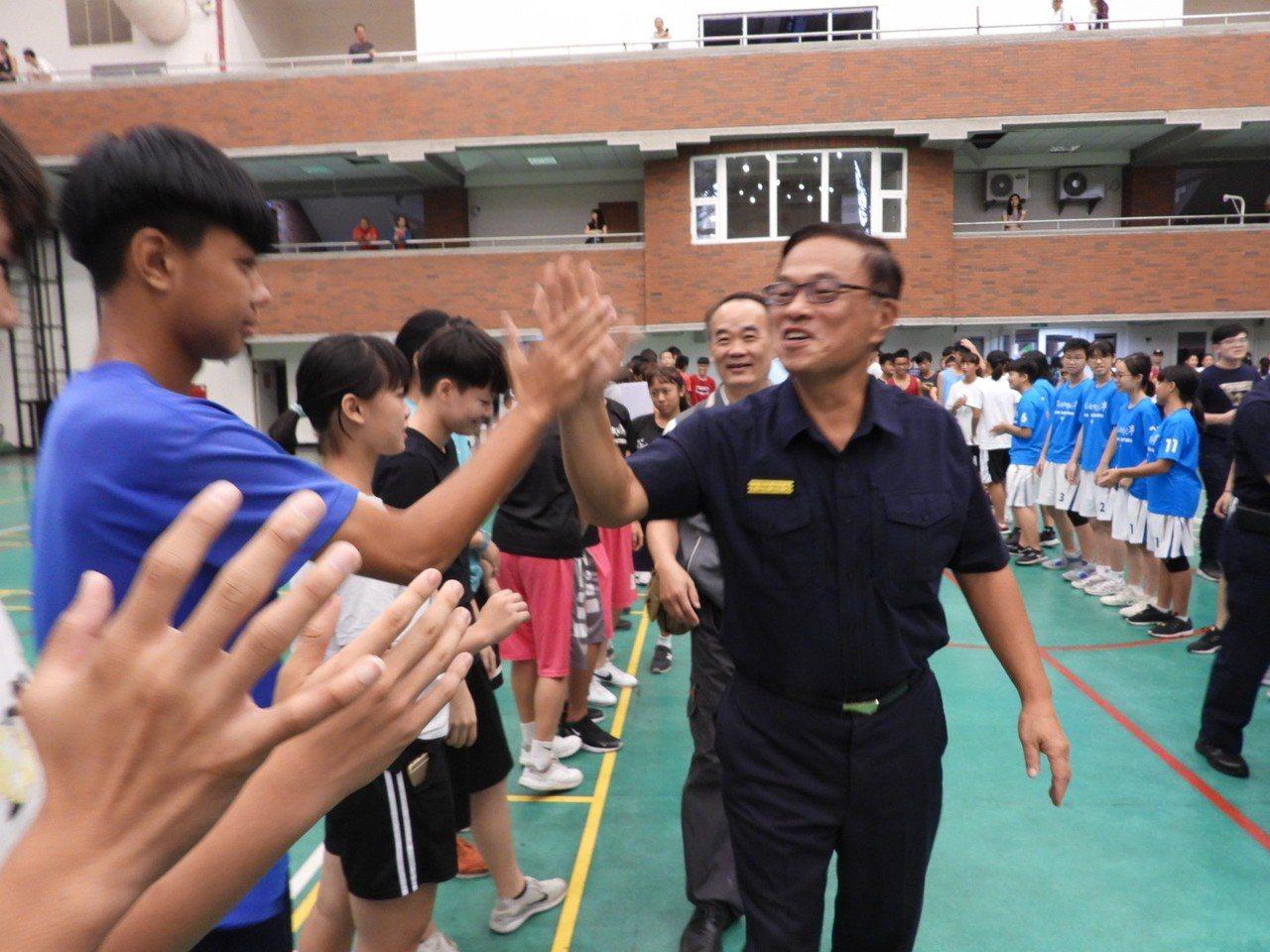 台南市警察局長黃宗仁進場時與成列歡迎的學生一一擊掌,展現巨星般風采。記者周宗禎/...