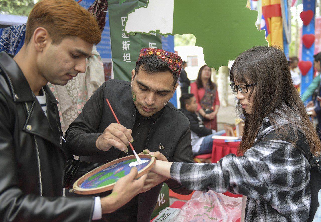 山東大學第18屆國際文化風情展4月26日在濟南舉行,巴基斯坦留學生為參觀者塗上民...
