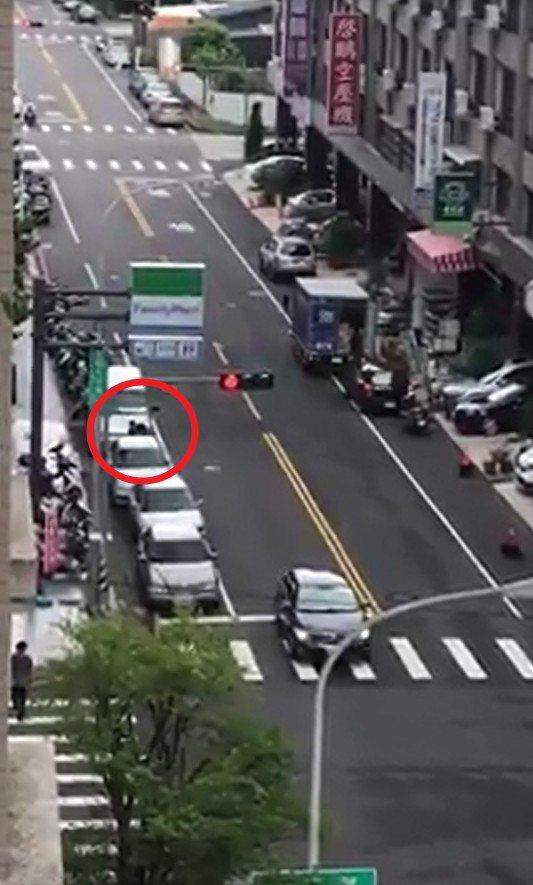 一名男子(紅色圓圈處)行為失控無端攻擊路旁車輛,巨大聲響驚醒附近住戶查看。圖/擷...