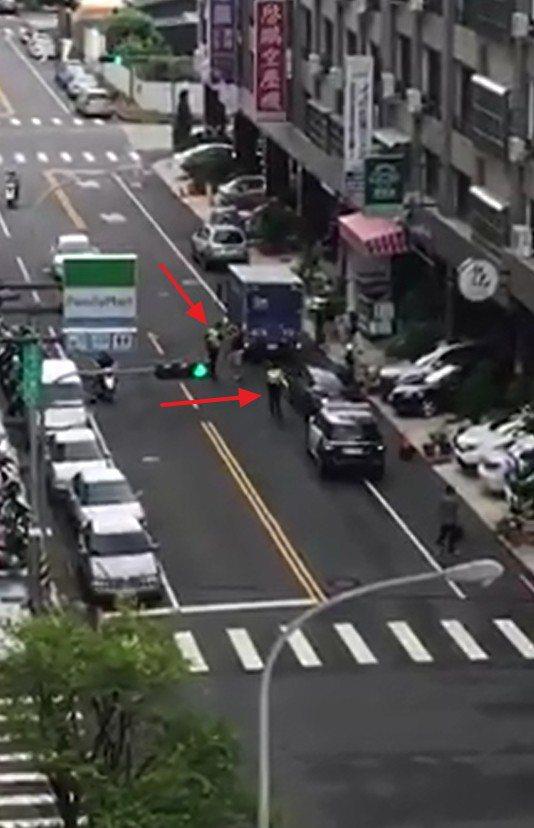 一名男子行為失控無端攻擊路旁車輛,兩名員警(紅色箭頭處)到場處理,並將男子帶回所...