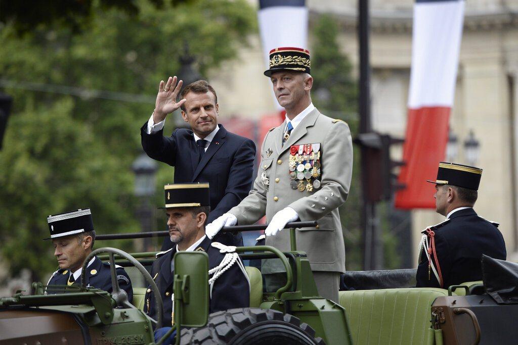 法國國慶日,總統馬克宏站在軍車上,沿著香榭麗舍大道抵達閱兵式舉行現場。 美聯社