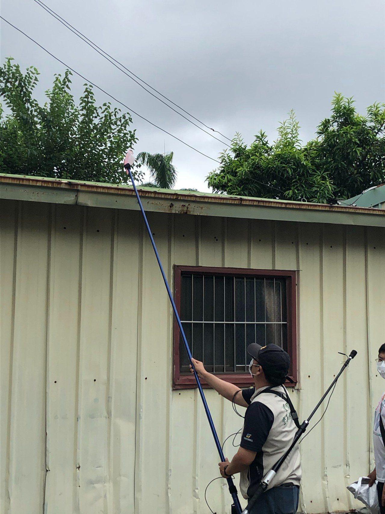 台南市防疫人員針對屋頂天溝自製工具進行防疫。圖/衛生局提供
