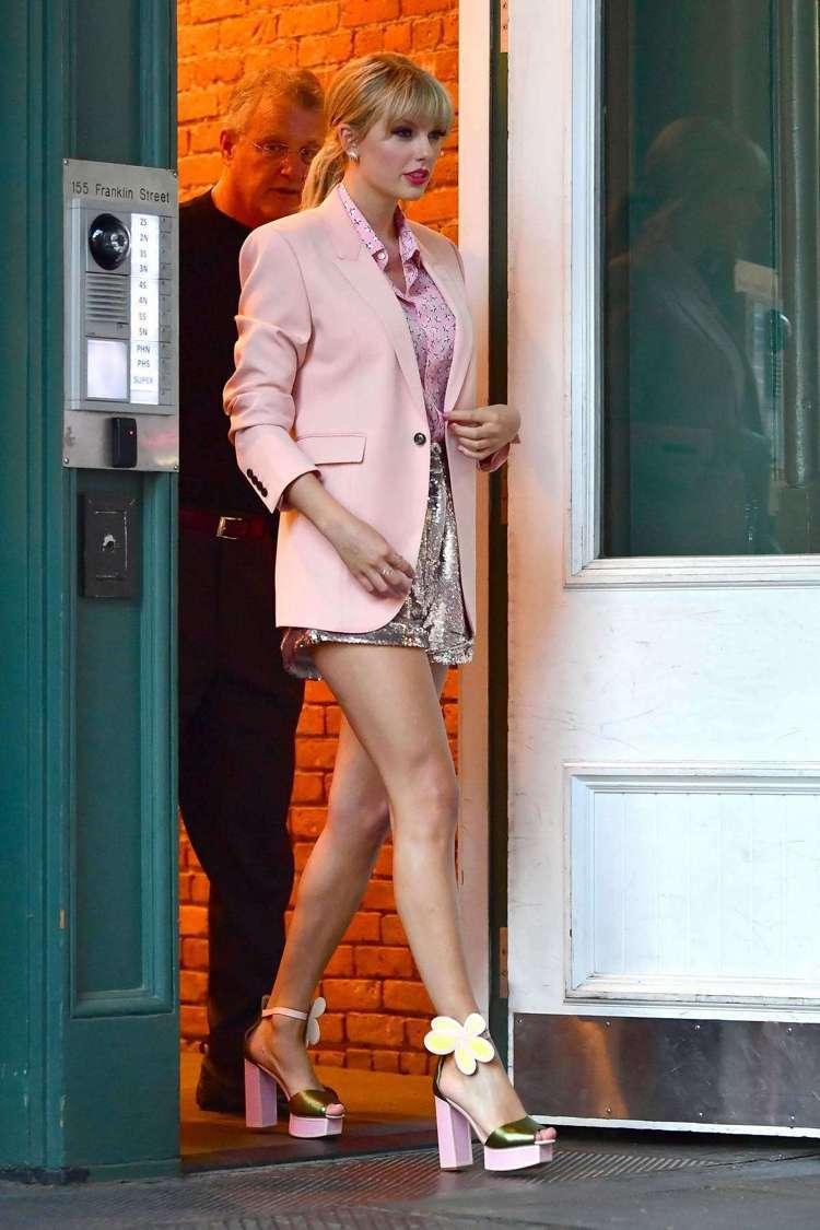 泰勒絲穿粉紅色西裝搭同色襯衫巧妙配上IRO的香檳金亮片短褲、花朵裝飾粗跟高跟鞋,...
