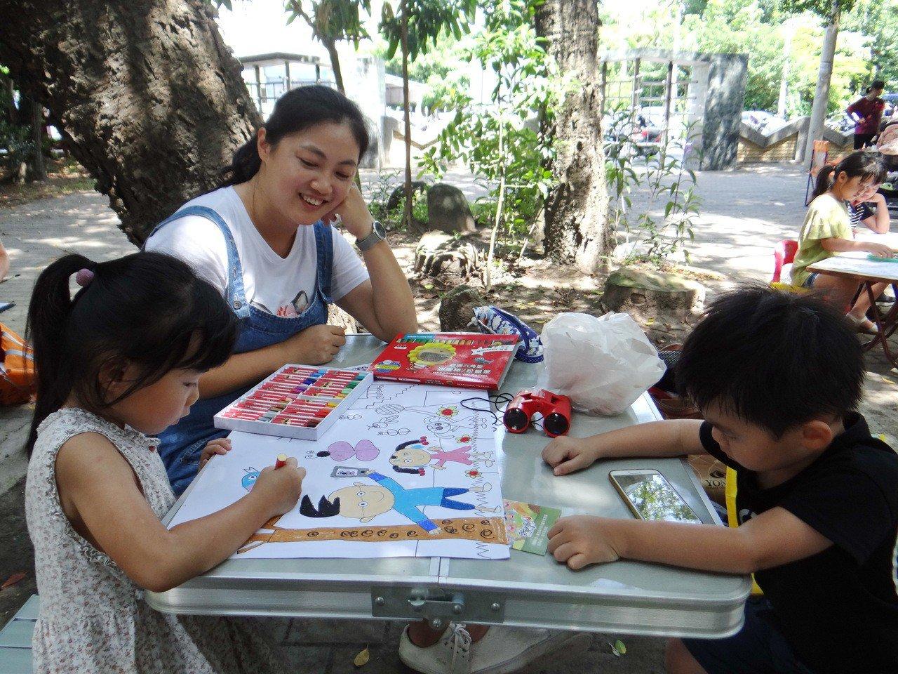 大樹下姊姊忙畫畫,弟弟看手機,兩種不同的彩色世界,帶著孩子一起成長。記者蔡維斌/...