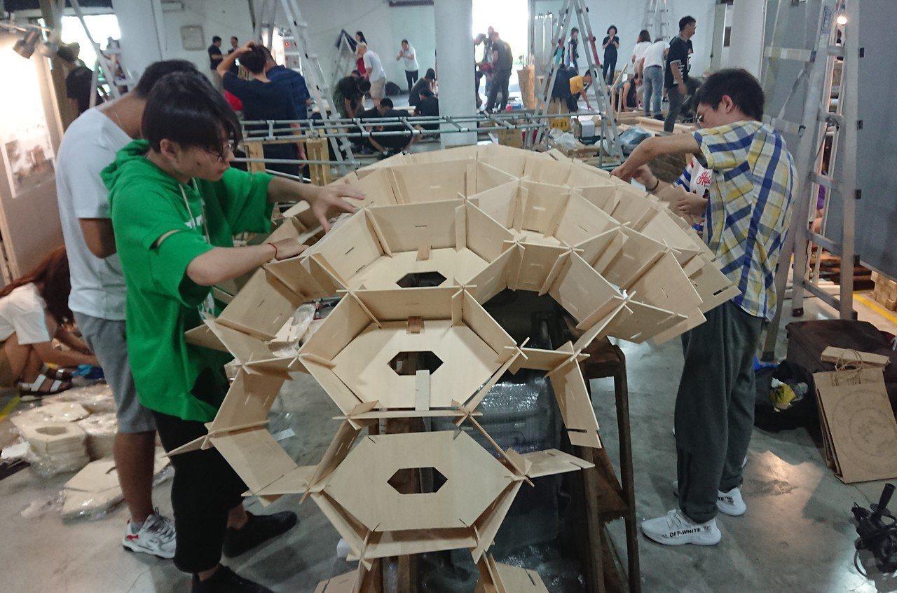 參賽學生隊伍在比賽一開始高呼加油口號,隨即忙著將已裁切、編號的木材依序排列,展開...