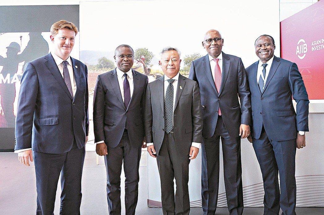 亞投行行長金立群(中)與三個新成員國官方代表合影。  中新社