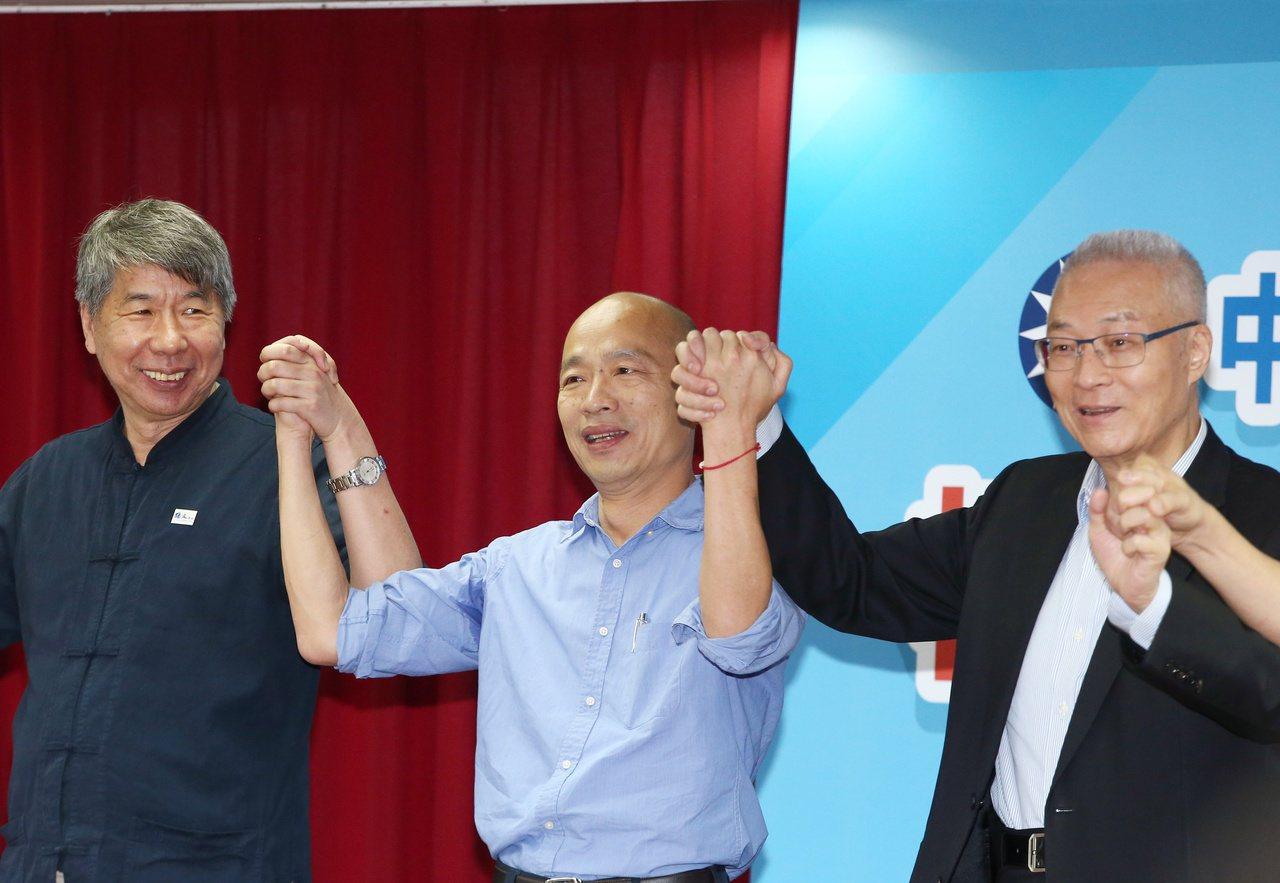 國民黨黨內初選民調韓國瑜勝出,張亞中(左)與黨主席吳敦義(右)牽起韓國瑜的手,高...