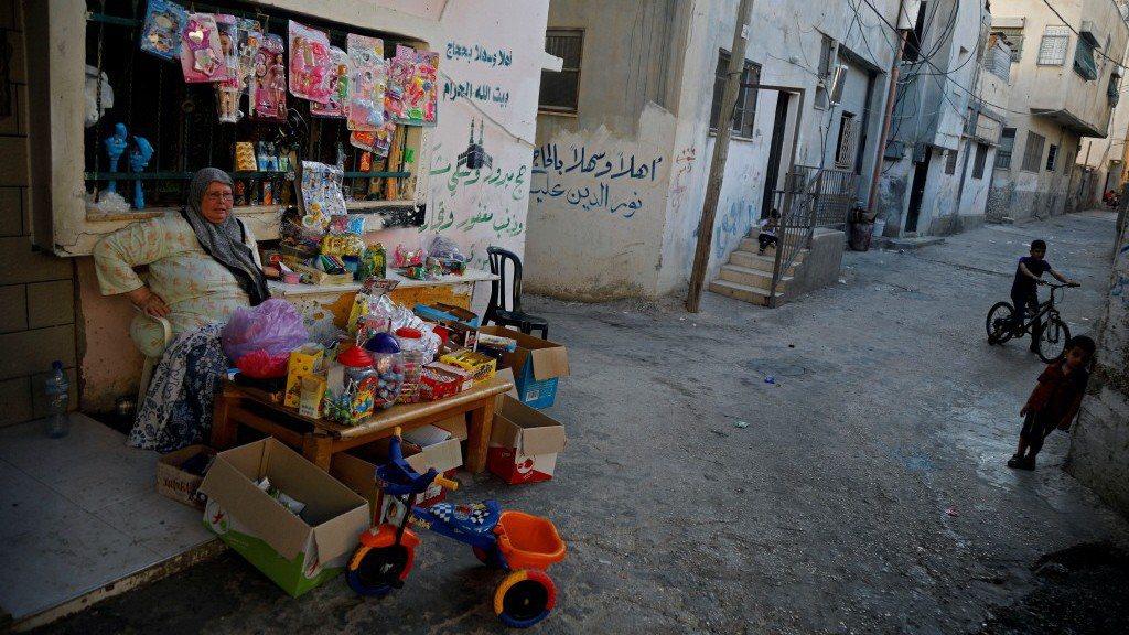 一名巴勒斯坦婦女在約旦河西岸的難民營賣小吃和玩具。路透社