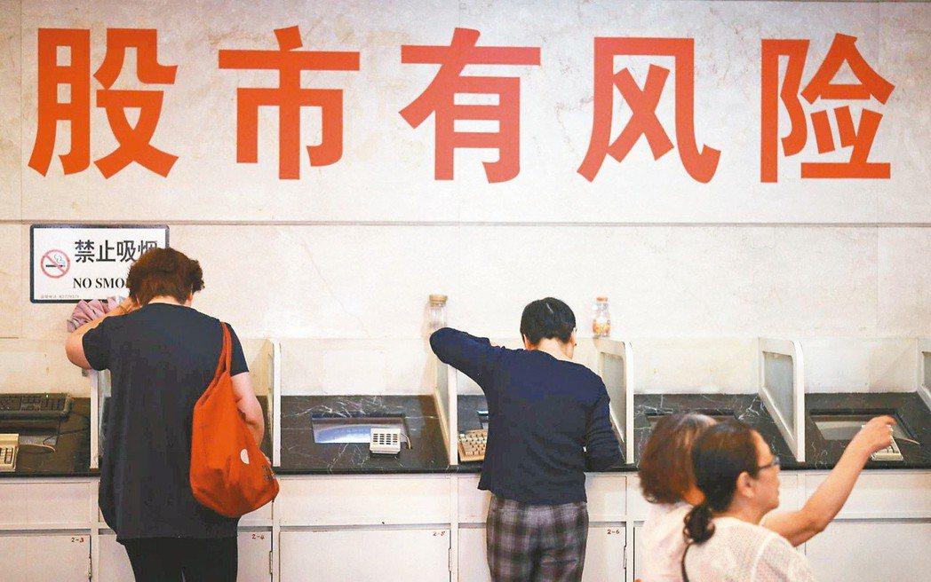 近年來有不少台灣股市名嘴西進上海,到大陸股市淘金。圖為大陸股民在上海一家號子內看...