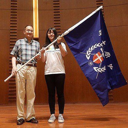 中原大學校長張光正(左)將象徵責任與傳承的旗幟傳授給國際志工,期許大家用專業在異...