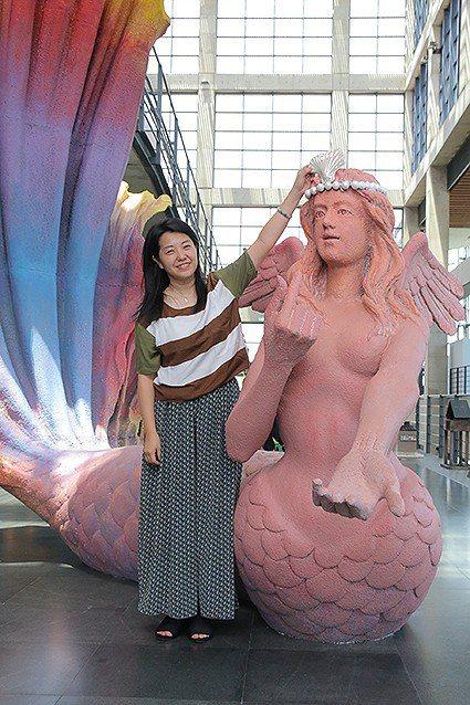新北市文化局長蔡佳芬把特製的陶瓷貝殼襄在藝術家游忠平作品《我愛超級美人魚》的頭飾...
