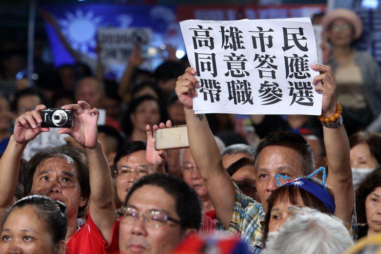 一名韓國瑜支持者手舉「高雄市民同意答應帶職參選」標語,表達對高雄市長韓國瑜投入2...