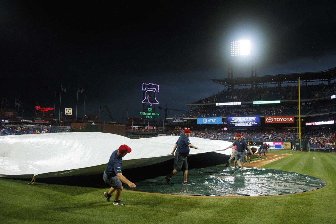 費城人主場比賽因雨拉起帆布,沒想到竟有人在上面當成滑水道裸奔。 美聯社