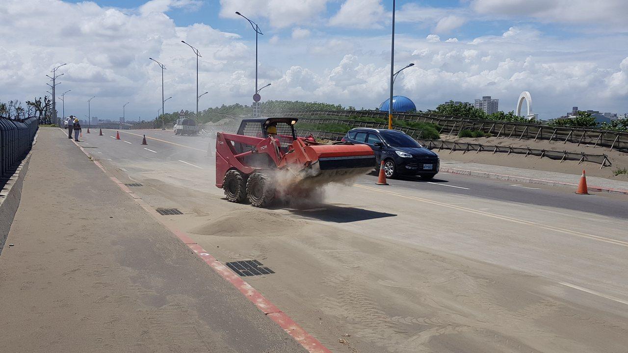新竹市南寮大道因颱風外圍環流漂沙嚴重,路面大片積沙,市府一早即請包商清理。記者黃...