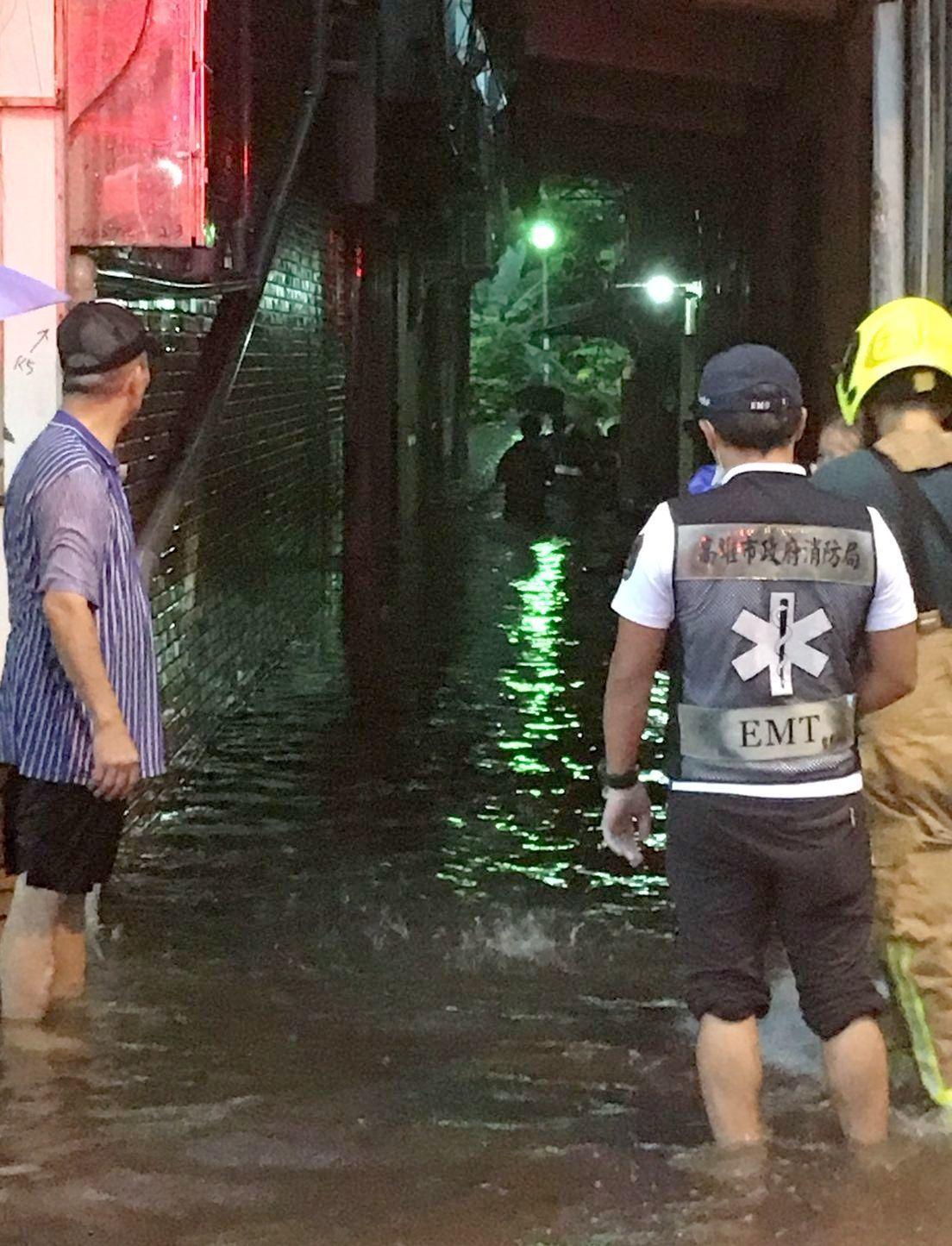 高雄市三民區建工路七四五巷今天淹水及腰,消防人員涉水進巷內,幫行動不便的住戶抬上...