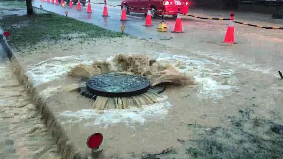 高雄市鳥松區神農路遇大雨積水嚴重,大量雨水從人孔蓋中溢出路面。圖/ 高雄市議員邱...