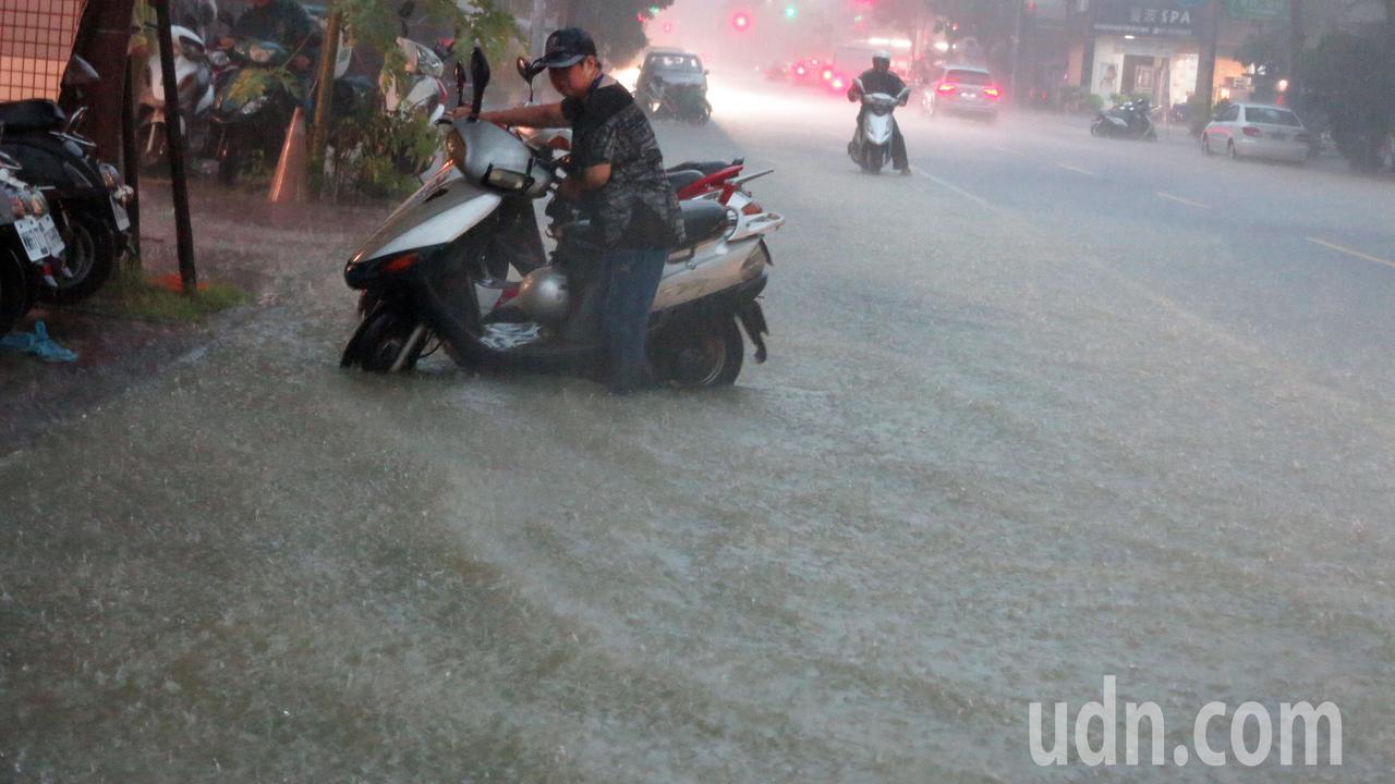 高雄市區下午四點開始降下雷陣雨,超大雨勢讓許多路面積水,車輛拋錨動彈不得,民眾只...