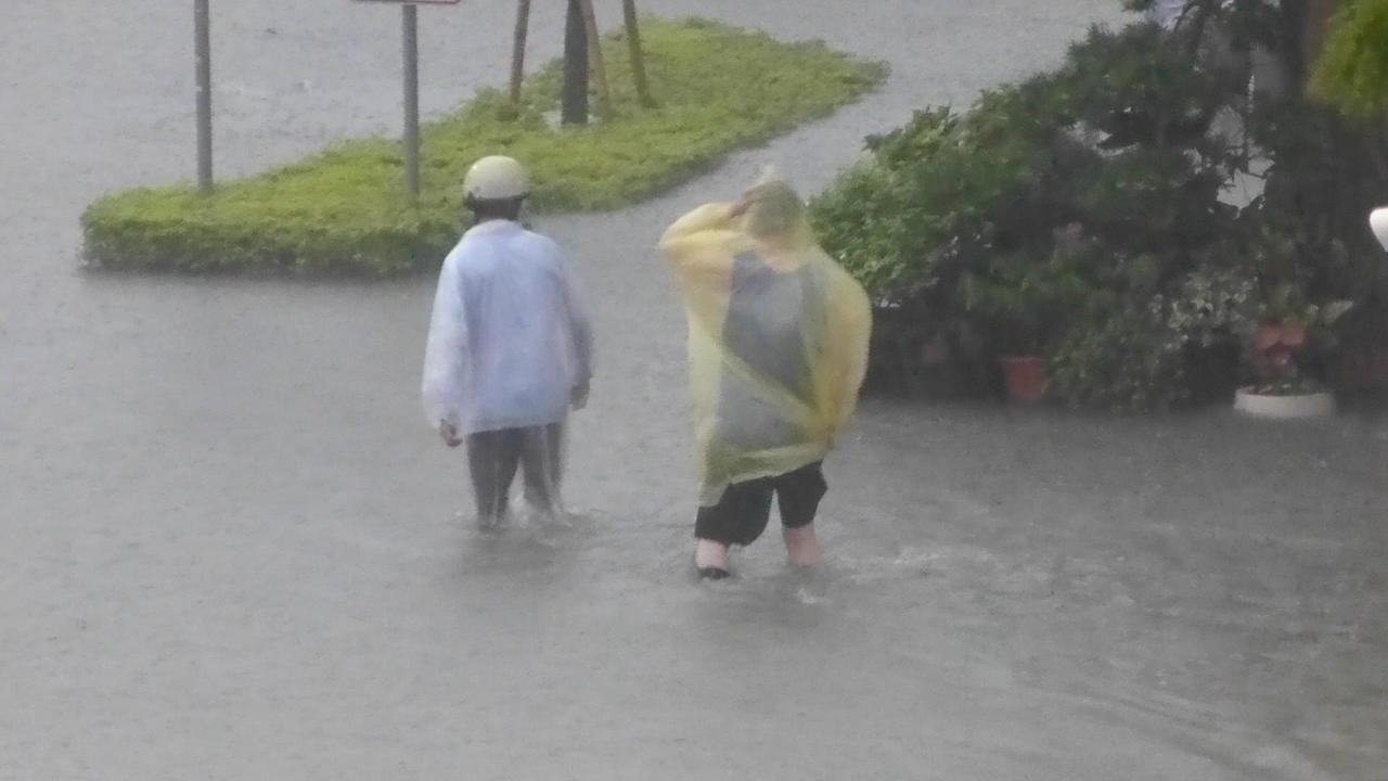 高雄市下午的雷陣雨造成多處積水嚴重,兩名男子涉水走過鳳山府前路。記者楊濡嘉/攝影