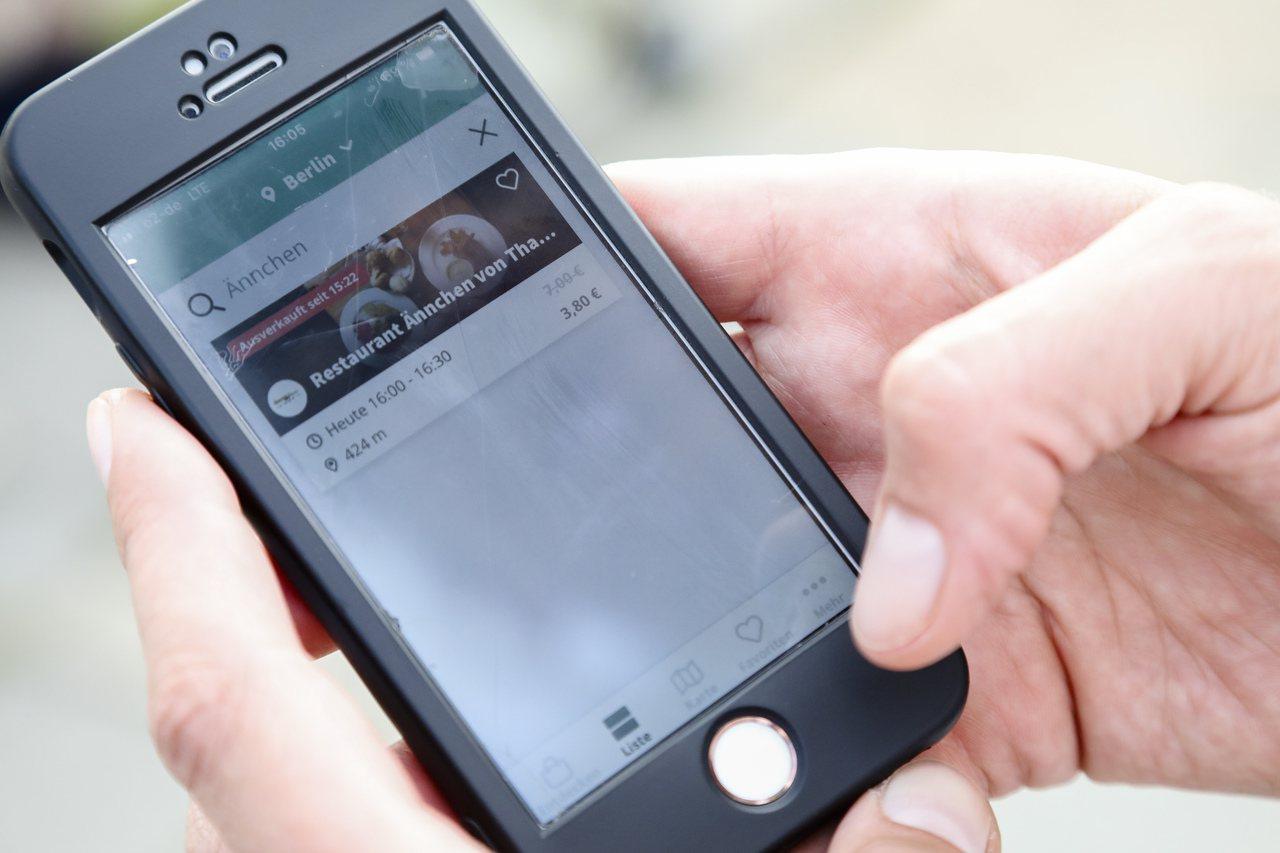 費辛格示範如何使用「好到不能丟」App。 (美聯社)