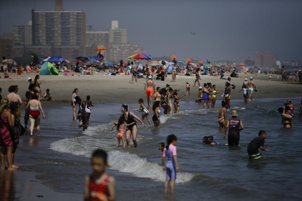 紐約市康尼島海邊擠滿戲水人潮。 (美聯社)
