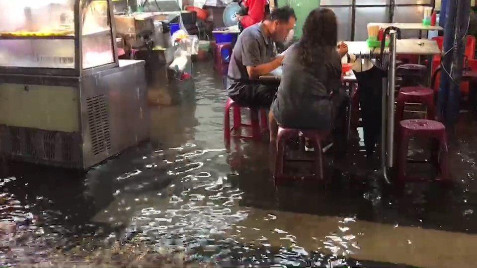一場暴雨使原本不淹水的北港市區,有民眾腳泡著水還能一邊吃飯,成為有趣的雨中即景。...
