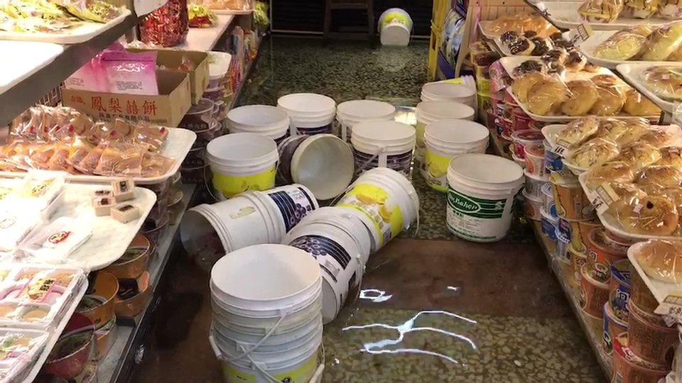 麵包店也泡水,裝糖果的桶子四處漂。記者蔡維斌/攝影