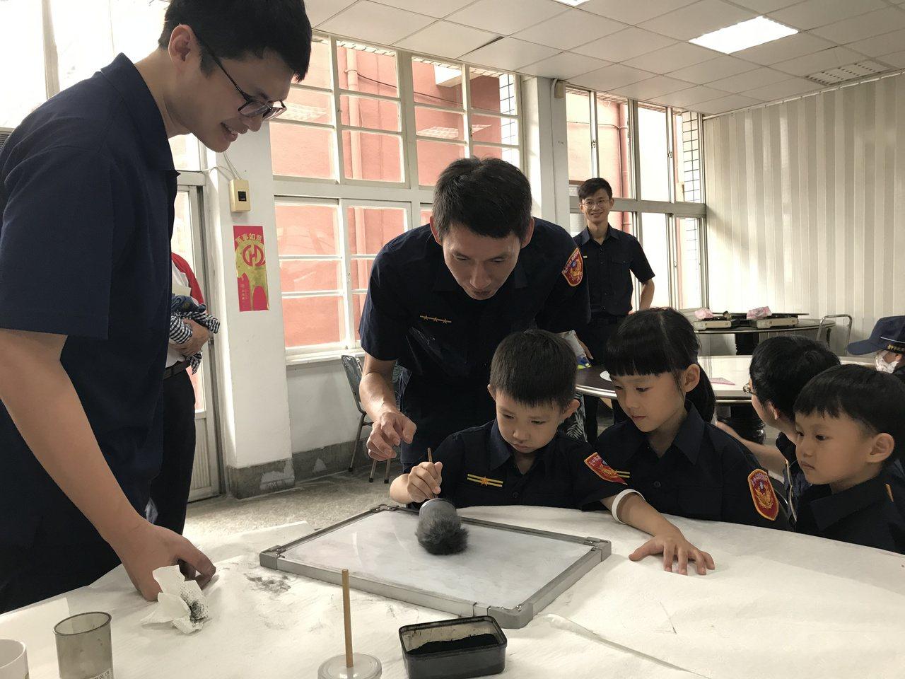 小朋友在鑑識闖關相當專注,與父母一起觀察碳粉的微妙變化。記者林佩均/攝影