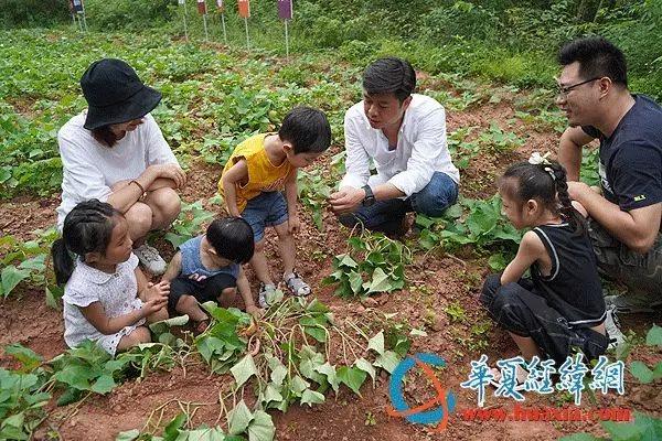 台灣青年許淵順向小朋友介紹紅薯的成長知識。(華夏經緯網)