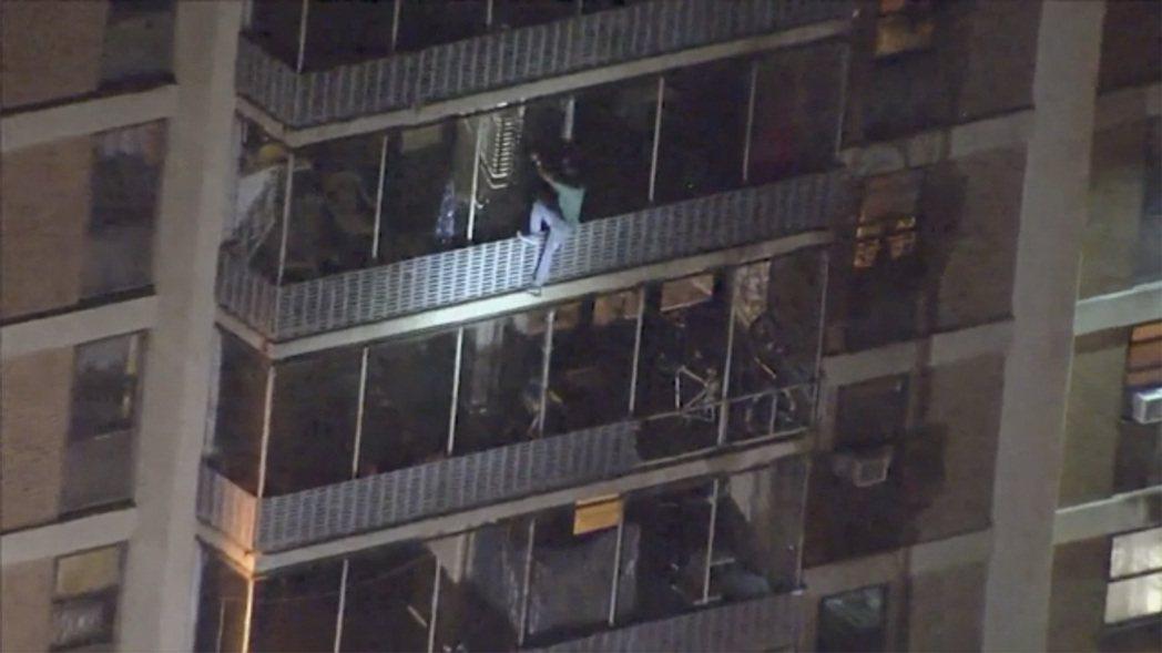 美國賓州費城一棟19層公寓大樓18日晚間發生火警,一名男子新聞台直升機拍到,靠著...