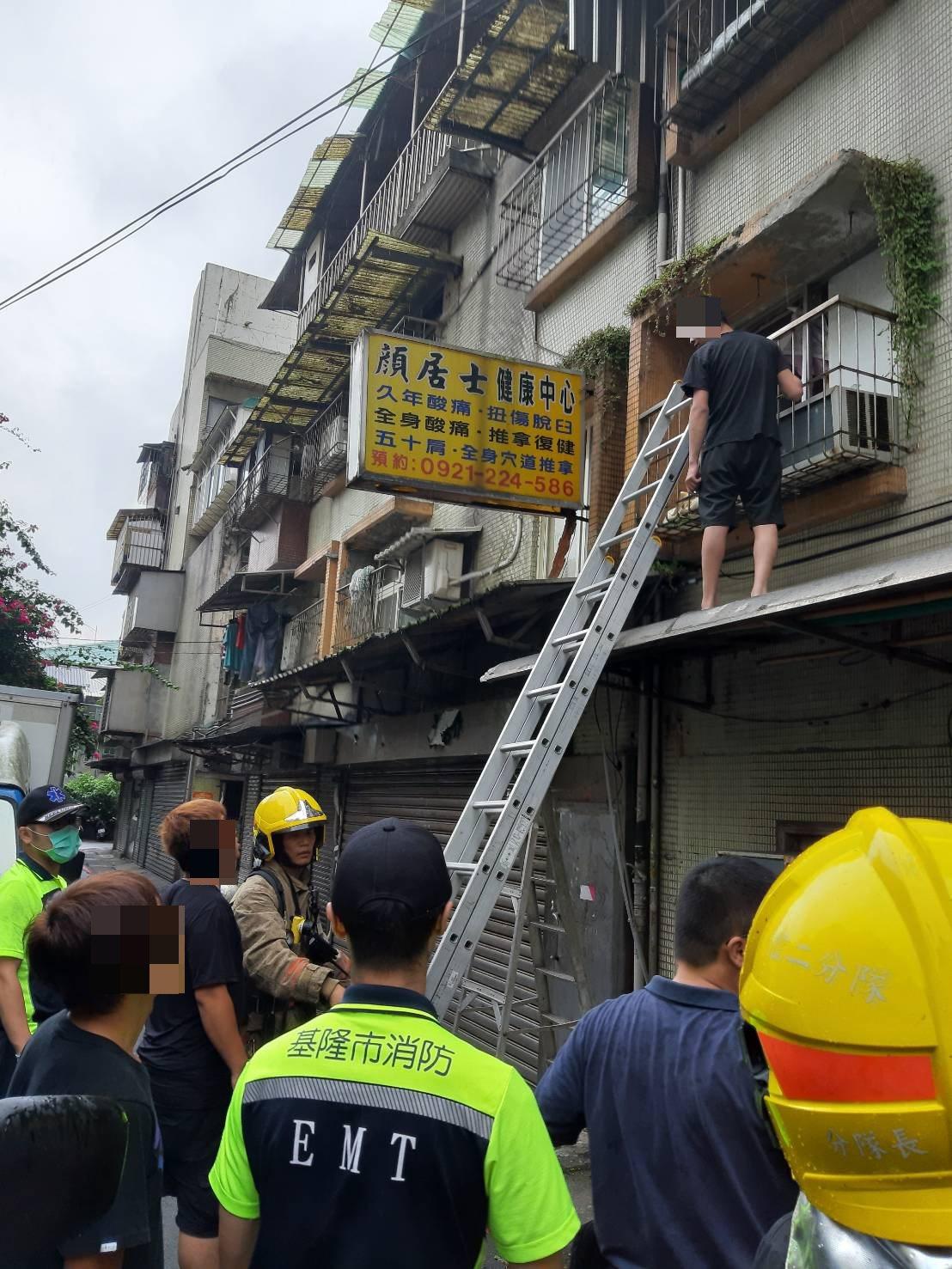 基隆市成功一路一處舊公寓今天下午4點多發生火警,消防隊員救出3名大人2名小孩共5...