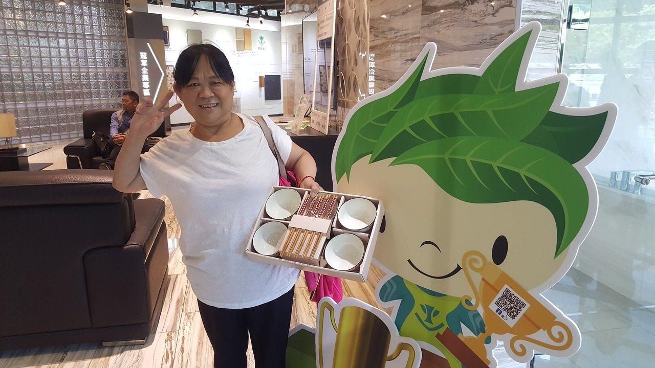 展夢園關懷身心障礙協會會員邱銀嬌開心地獲得精美的餐具組。記者胡蓬生/攝影