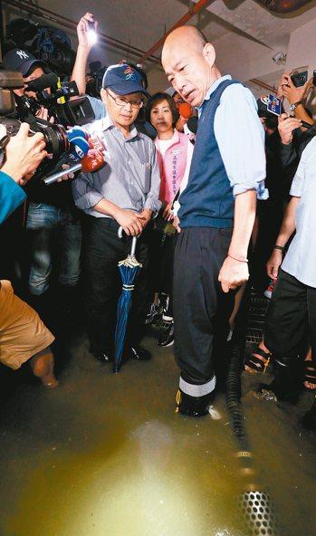 高雄市長韓國瑜(圖右)昨下午到苓雅區一棟大樓,了解地下室淹水災情。 記者劉學聖/...