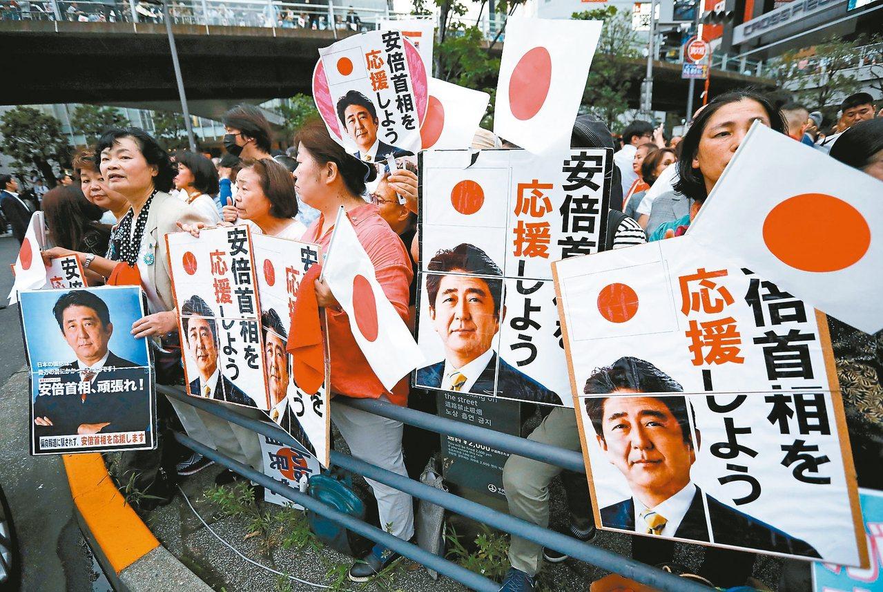 日本21日舉行參院選舉,首相安倍晉三的支持者在前一天的造勢場合等候他發表演說。 ...