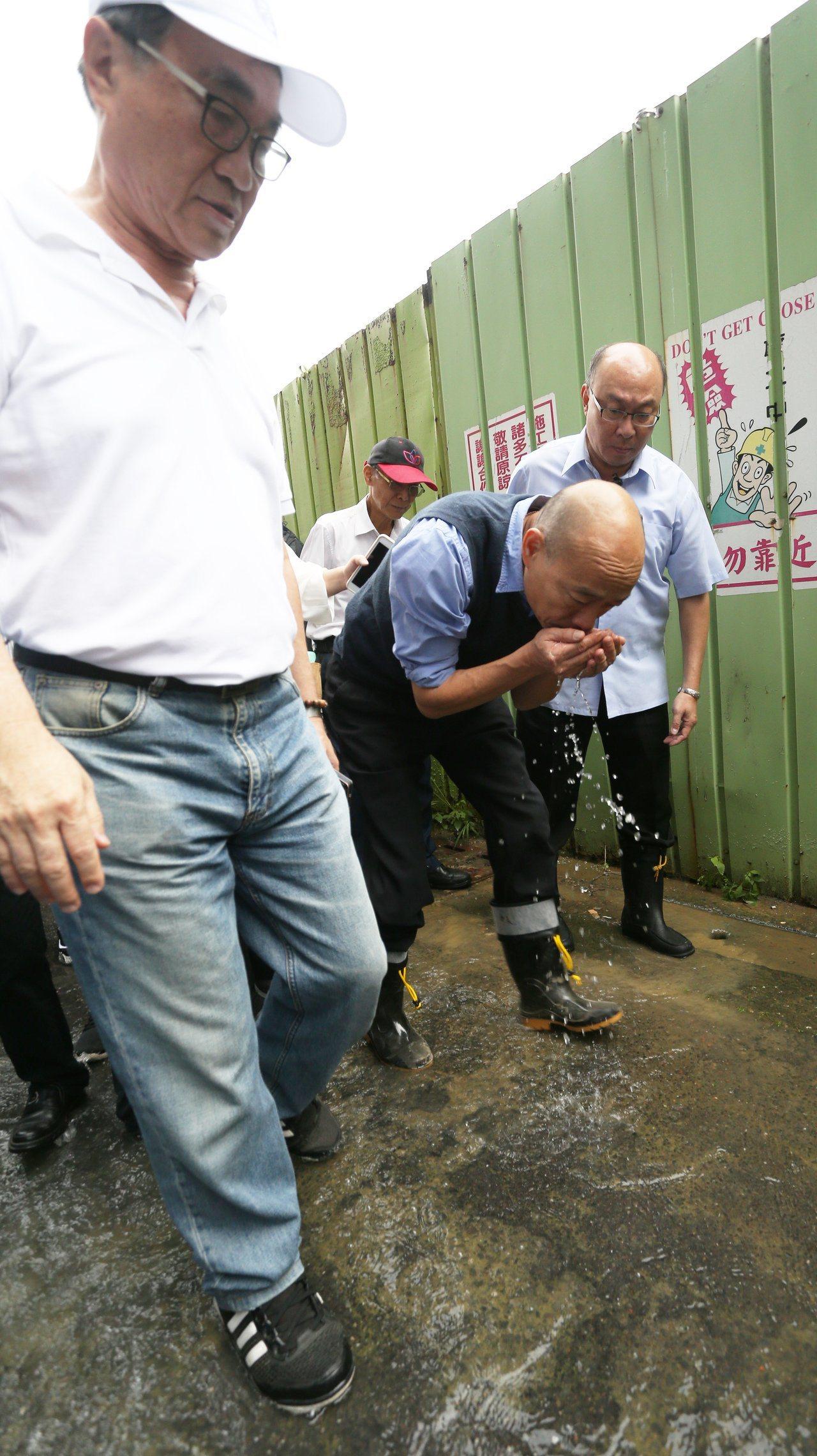 高雄市長韓國瑜20日到苓雅區一棟地下室因雨積水的大樓勘災時,先蹲下去掬一把水聞嗅...