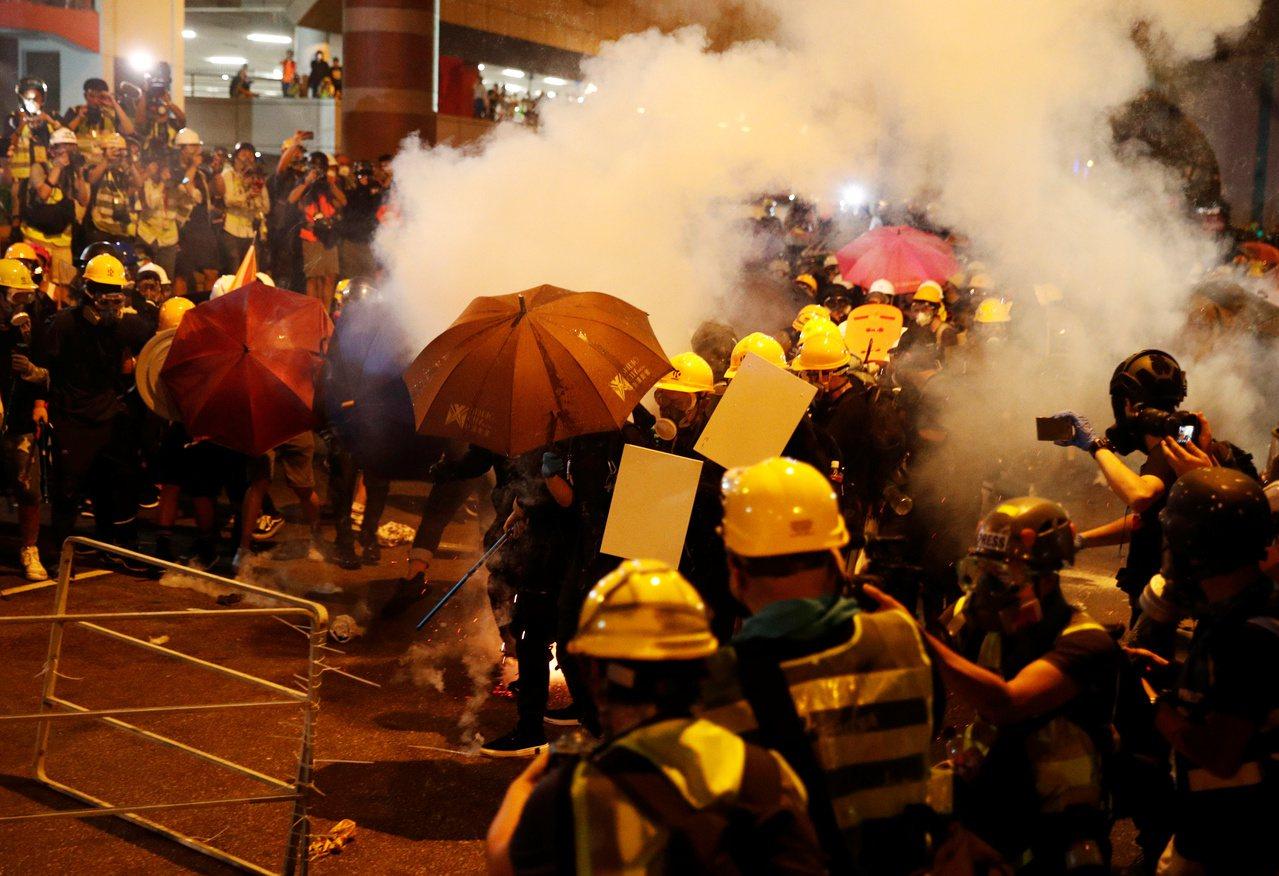 示威民眾21日晚間衝擊中共中央駐港聯絡辦公室後,港警晚間10點半後全力清場,發射...