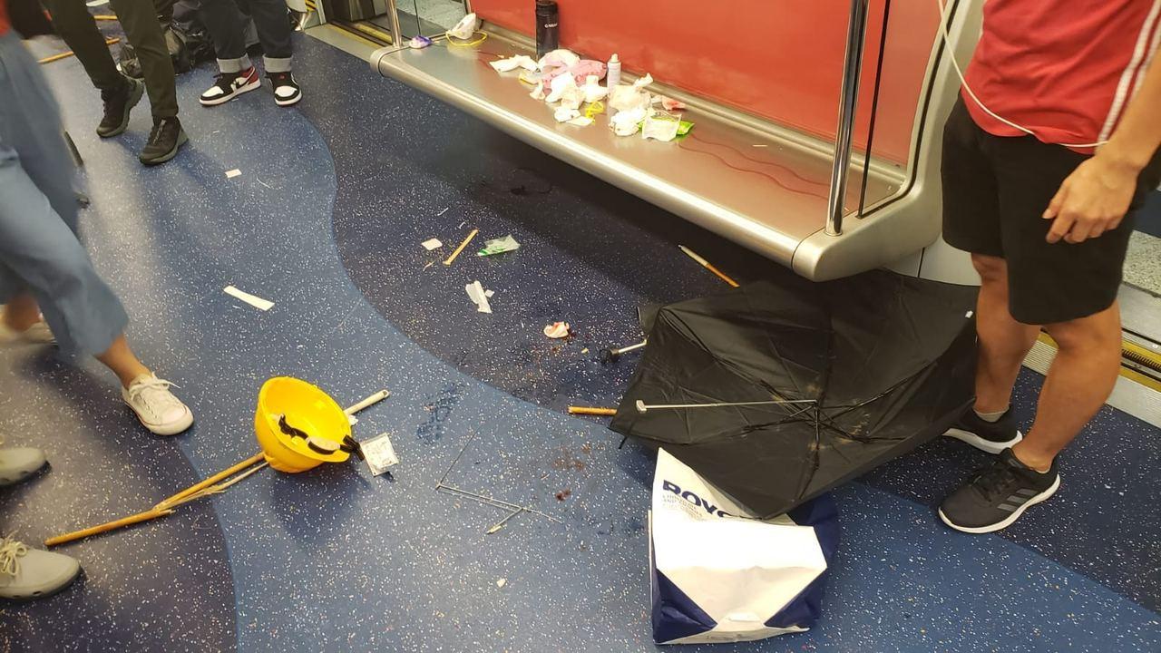 約晚上11時05分,白衣人士開始朝車廂內的市民扔竹枝、雨傘等雜物。圖擷自香港01