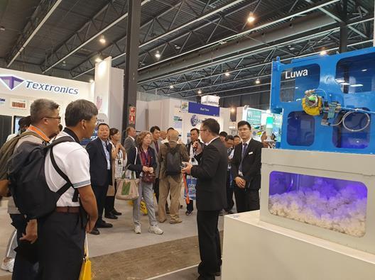 詹正田董事長(左三)與參觀團團員參觀Luwa紡織空調系統展商。 紡拓會/提供