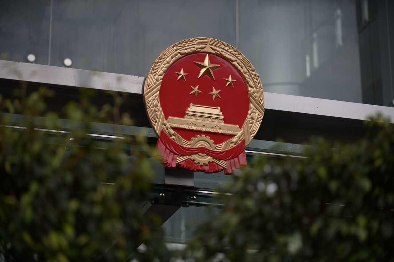 中聯辦職員深夜將中共國徽拆下清理,其後再將新的國徽掛回門上。取自星島網