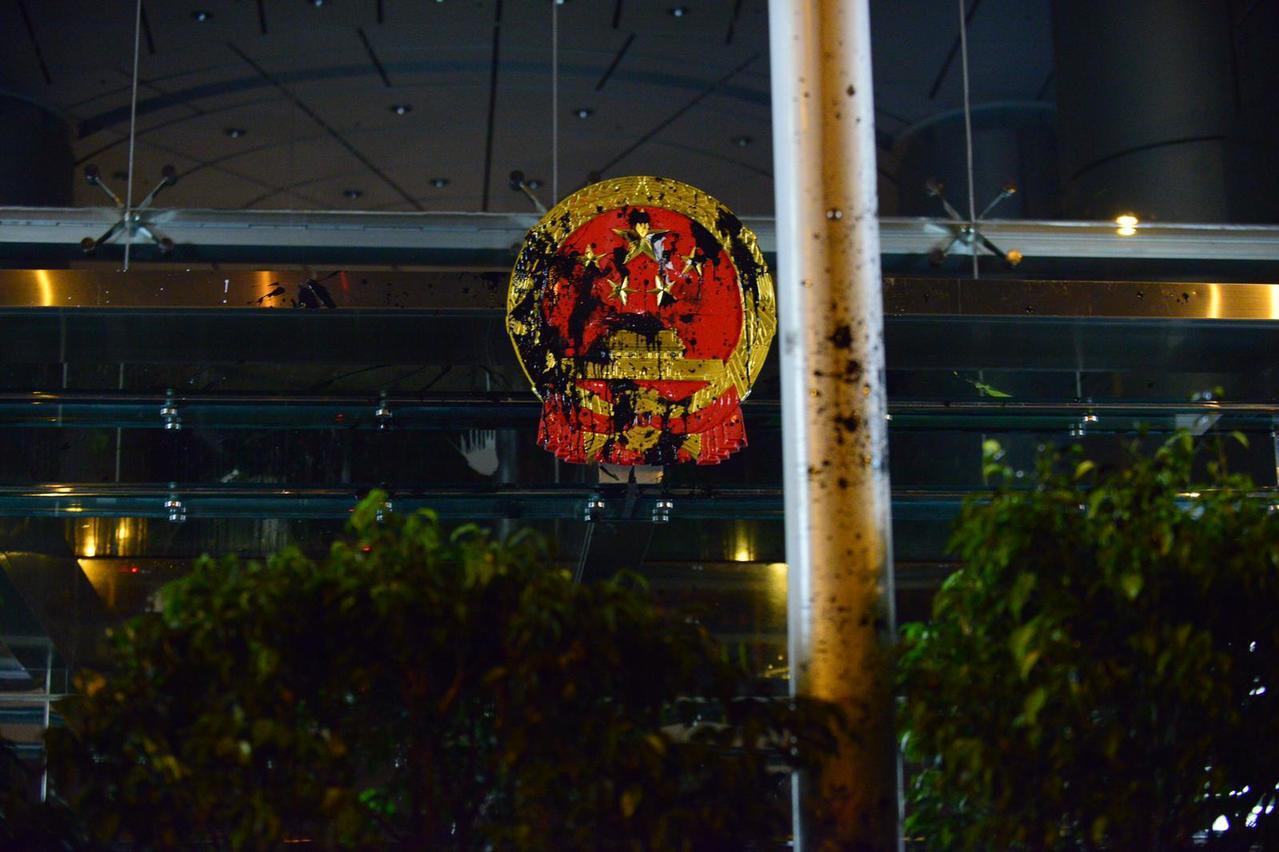 示威者昨晚向中聯辦大樓及中共國徽投擲雞蛋和淋潑油漆。取自星島網