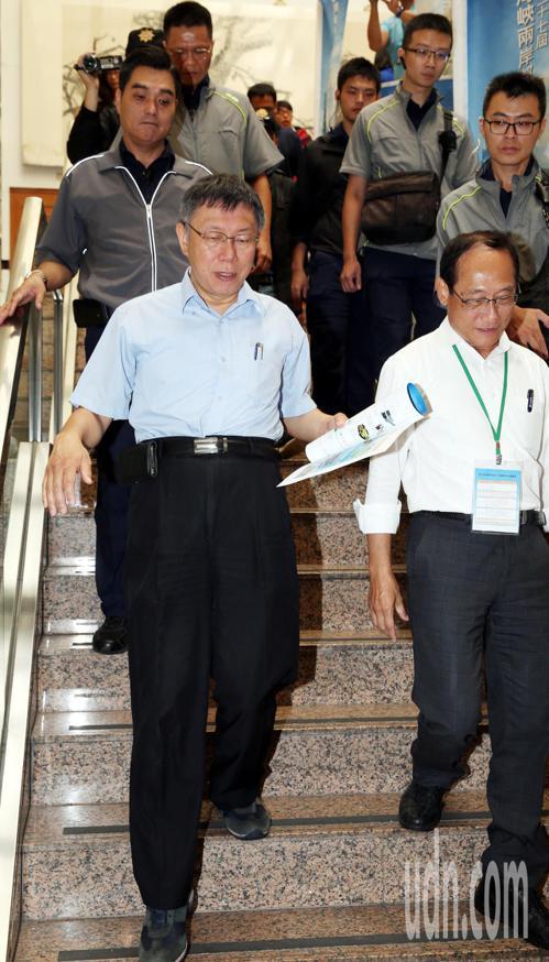 台北市長柯文哲(前左)在大批維安人員陪同下離開「海峽兩岸都市交通學術研討會」會場...